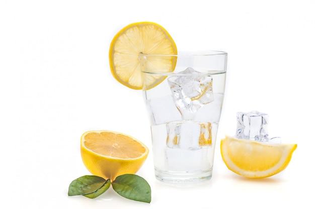 Acqua, limone e cubetti di ghiaccio in un bicchiere. fette di limone e lino accanto a un bicchiere. isolato.