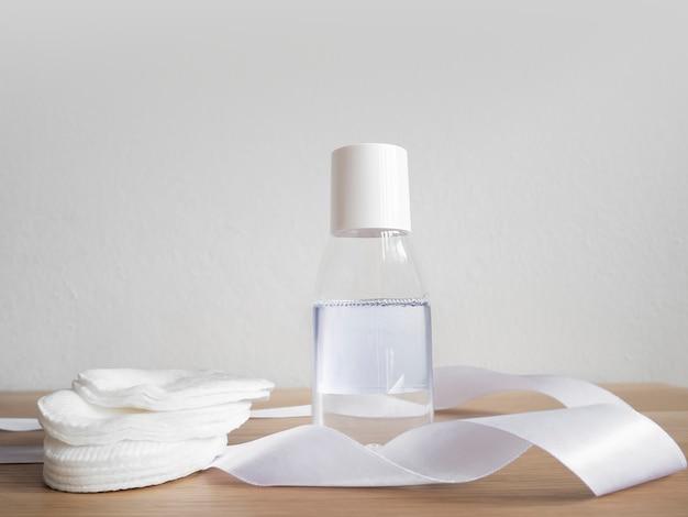 Acqua micellare con tamponi di cotone sul tavolo di legno e parete bianca.