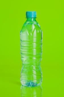 Acqua minerale chiara e pura su uno sfondo verde brillante