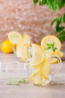 Acqua minerale rinfrescante con cubetti di limone, menta e ghiaccio in bicchieri su un tavolo di legno