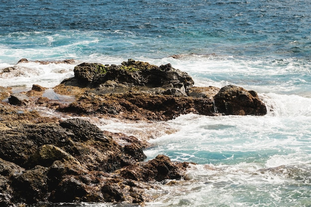 Acqua ondulata a lungo girato in riva rocciosa