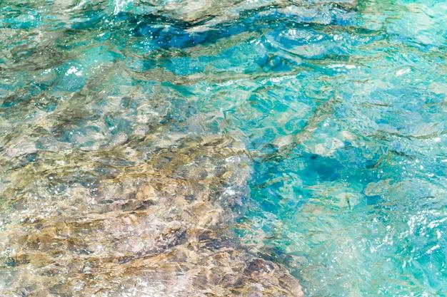 Acqua ondulata cristallina del primo piano alla spiaggia