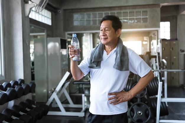 Acqua potabile assetata asiatica dell'uomo senior dopo l'esercizio nella palestra di forma fisica. stile di vita sano degli anziani.