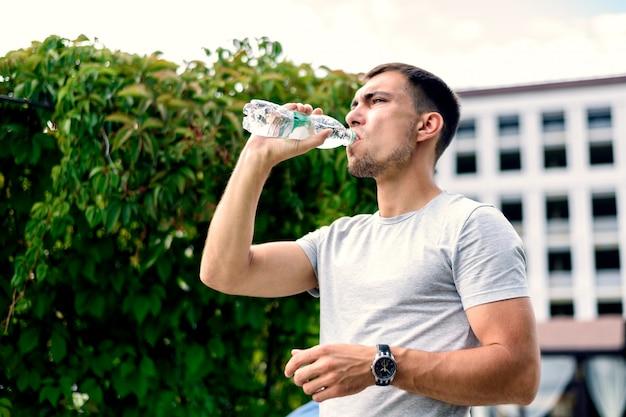 Acqua potabile del giovane uomo europeo dalla bottiglia di plastica su fondo dei cespugli verdi degli alberi il giorno soleggiato luminoso