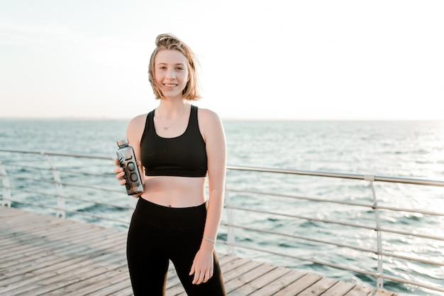 Acqua potabile dell'adolescente sportivo in forma su una spiaggia durante l'allenamento