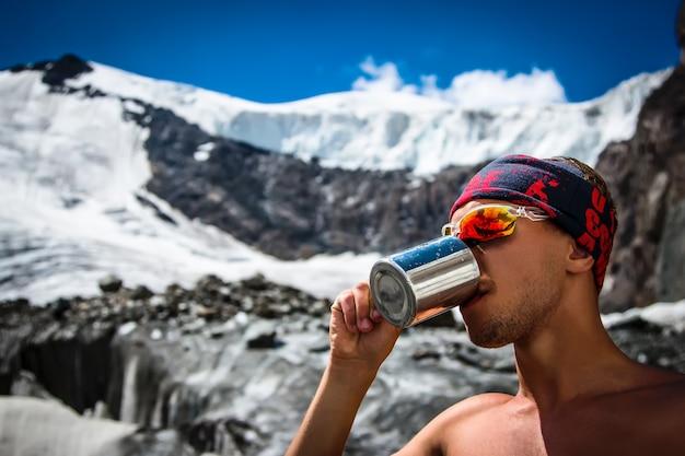 Acqua potabile dell'alpinista maschio da una tazza su un ghiacciaio nelle vacanze attive di concetto di stile di vita di viaggio delle montagne