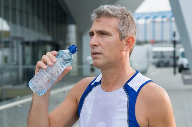 Acqua potabile dell'uomo atletico dopo aver eseguito la sessione