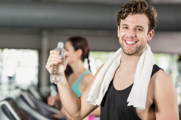 Acqua potabile dell'uomo atletico mentre correndo sulla pedana mobile in palestra