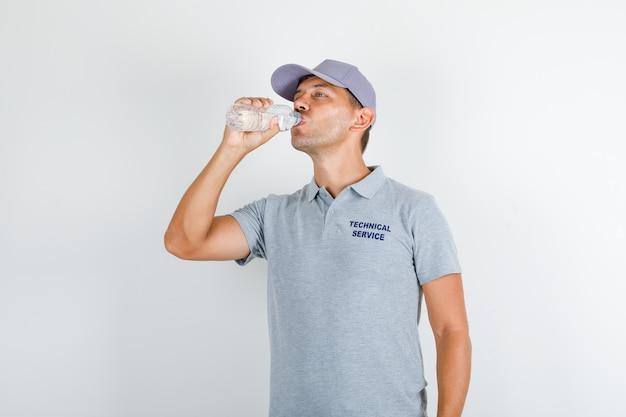 Acqua potabile dell'uomo di servizio tecnico in maglietta grigia con il cappuccio