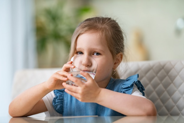 Acqua potabile della bambina sveglia in cucina a casa