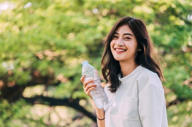 Acqua potabile della bella donna al parco di verde di estate. concetto di stile di vita sano