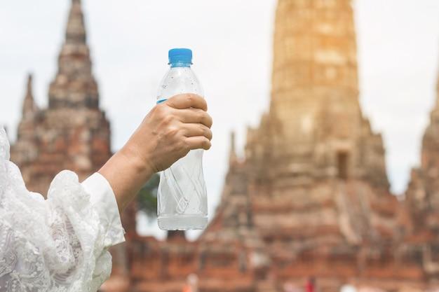 Acqua potabile della bella giovane donna asiatica dopo la camminata di riposo in festa