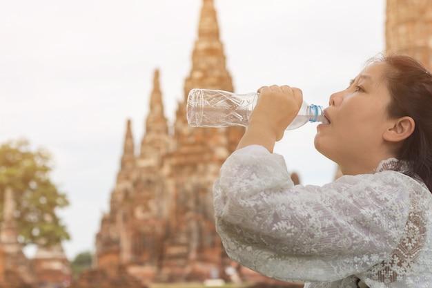 Acqua potabile della bella giovane donna asiatica dopo la camminata di riposo in vacanza al tempio di wat chai watthanaram, bottiglia femminile della tenuta del viaggiatore di acqua pura