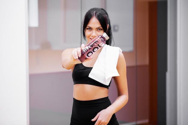 Acqua potabile della bevanda della giovane donna nella palestra di forma fisica