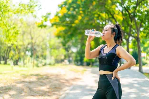 Acqua potabile della donna asiatica in abbigliamento sportivo