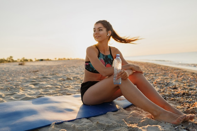 Acqua potabile della donna dell'atleta di bella forma fisica dopo il lavoro fuori che si esercita sull'estate di sera di tramonto in spiaggia. abbigliamento sportivo alla moda.
