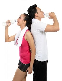 Acqua potabile della donna e dell'uomo dopo forma fisica