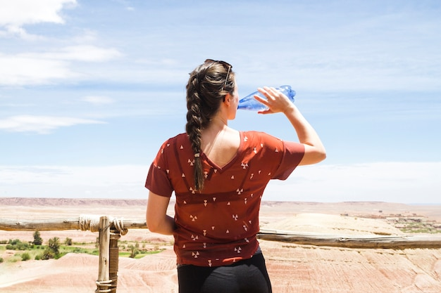 Acqua potabile della donna nel paesaggio del deserto da dietro