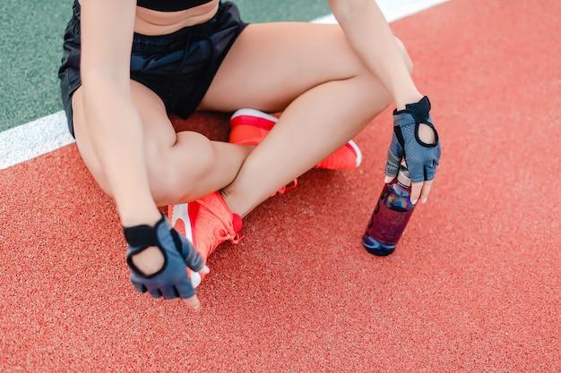 Acqua potabile della donna sportiva adatta dalla bottiglia sullo stadio durante l'allenamento di forma fisica