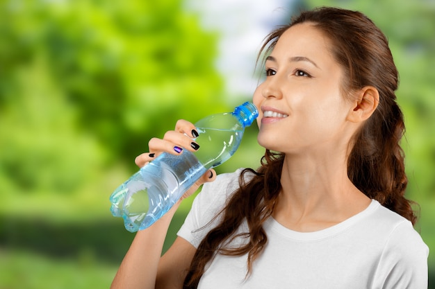 Acqua potabile della donna sportiva all'aperto il giorno soleggiato
