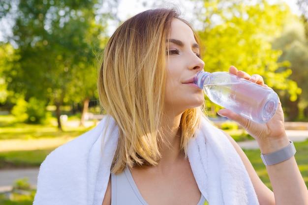 Acqua potabile della giovane bella donna durante la mattina che pareggia nel parco