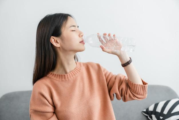 Acqua potabile della giovane donna asiatica da una bottiglia a casa