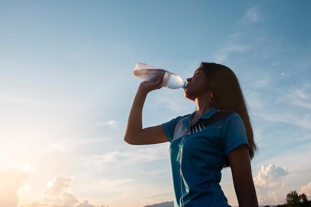 Acqua potabile della giovane donna asiatica dopo avere pareggiato