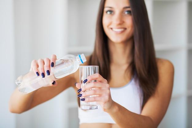 Acqua potabile della giovane donna. bella ragazza che tiene la bottiglia d'acqua