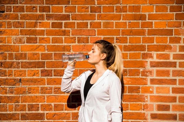 Acqua potabile della giovane donna da una bottiglia