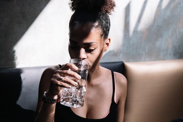 Acqua potabile della giovane donna di colore che si siede su un sofà