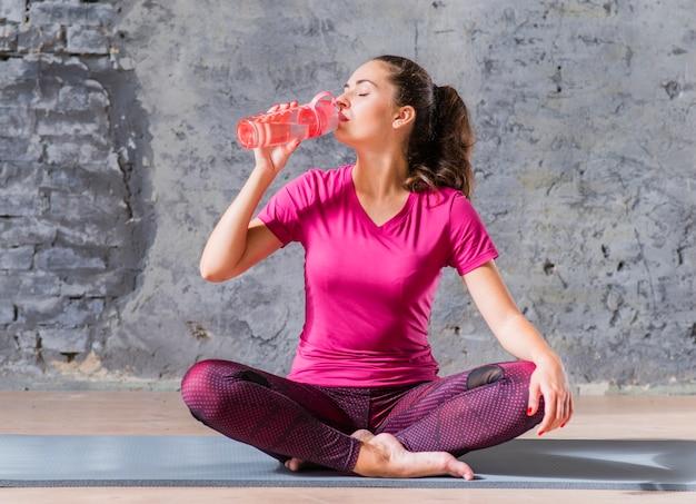 Acqua potabile della giovane donna di forma fisica dalla bottiglia