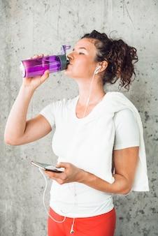 Acqua potabile della giovane donna e ascoltare musica sullo smartphone
