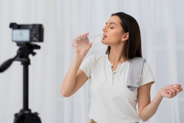 Acqua potabile della giovane donna sulla macchina fotografica
