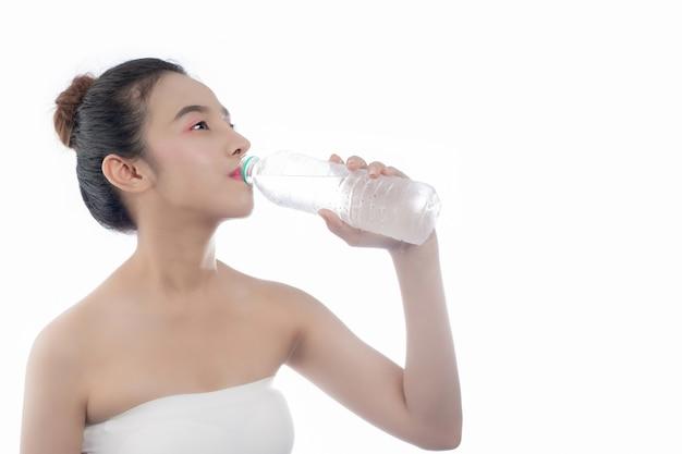 Acqua potabile della ragazza su una priorità bassa bianca.