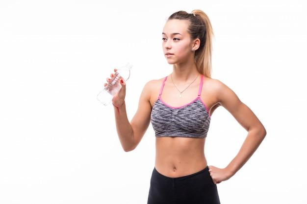 Acqua potabile della signora da una bottiglia trasparente su un bianco