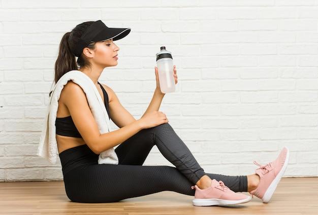 Acqua potabile di seduta e della giovane donna sportiva araba