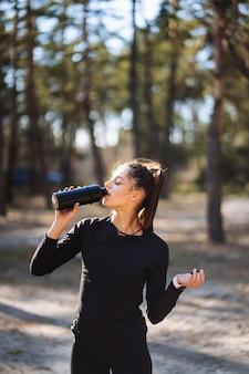 Acqua potabile esile della giovane donna dopo l'allenamento