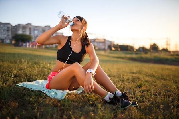 Acqua potabile sportiva della giovane donna. la ragazza si siede su una stuoia e ascolto musica in cuffia