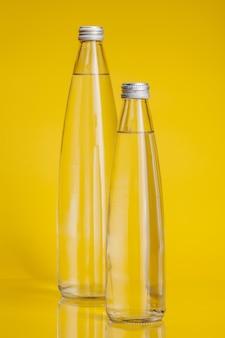 Acqua pura in bottiglia di plastica su sfondo giallo brillante