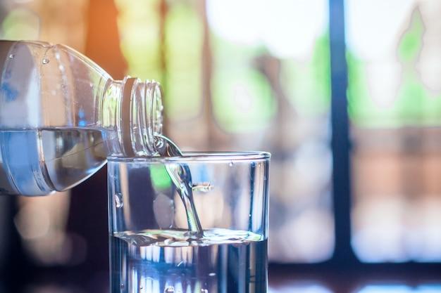 Acqua purificata della bevanda fresca di versamento dalla bottiglia sul fondo di vetro della tavola