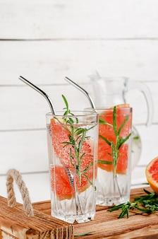 Acqua tonica di pompelmo con rosmarino su uno spazio di legno bianco. uno stile di vita sano. cannucce in metallo