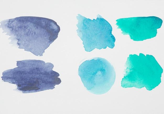 Acquamarina astratta e macchie blu di vernici su carta bianca
