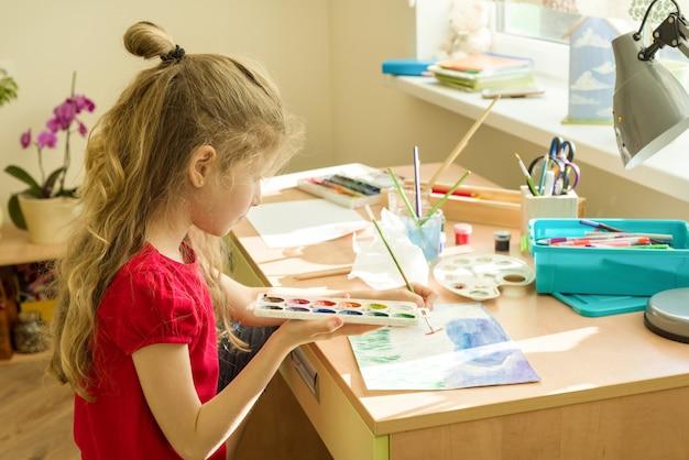 Acquerello del disegno del bambino della ragazza alla tavola a casa