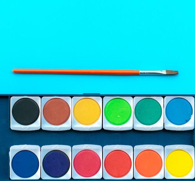 Acquerello e pennello messi sul tavolo di opere d'arte di vernice