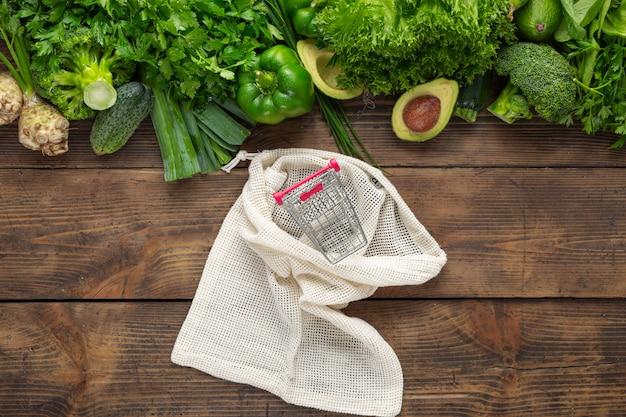 Acquista il concetto di cibo sano. sacchetto della spesa di vista superiore con il piccolo carrello e cibo pulito dell'alimento sano. verdura verde sulla vista di legno del piano d'appoggio