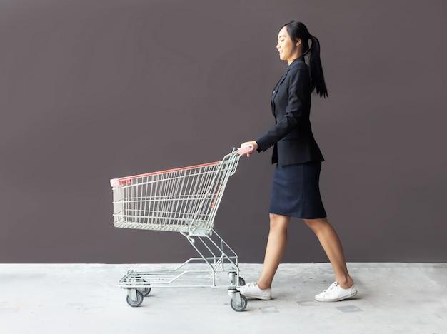 Acquisto asiatico della donna con il carrello di troley