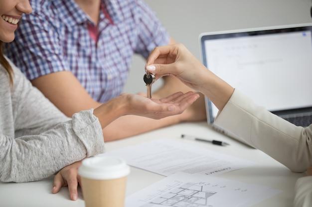 Acquisto del concetto della nuova casa, agente immobiliare che fornisce le chiavi alle coppie, primo piano