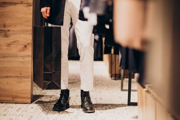 Acquisto del giovane al negozio di abbigliamento maschile