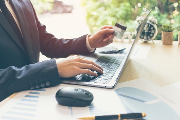 Acquisto dell'uomo d'affari e pagamento online che funzionano con il taccuino generico di progettazione con il ligh del sole