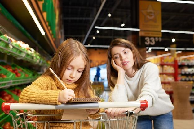 Acquisto della figlia piccola e della madre nel supermercato